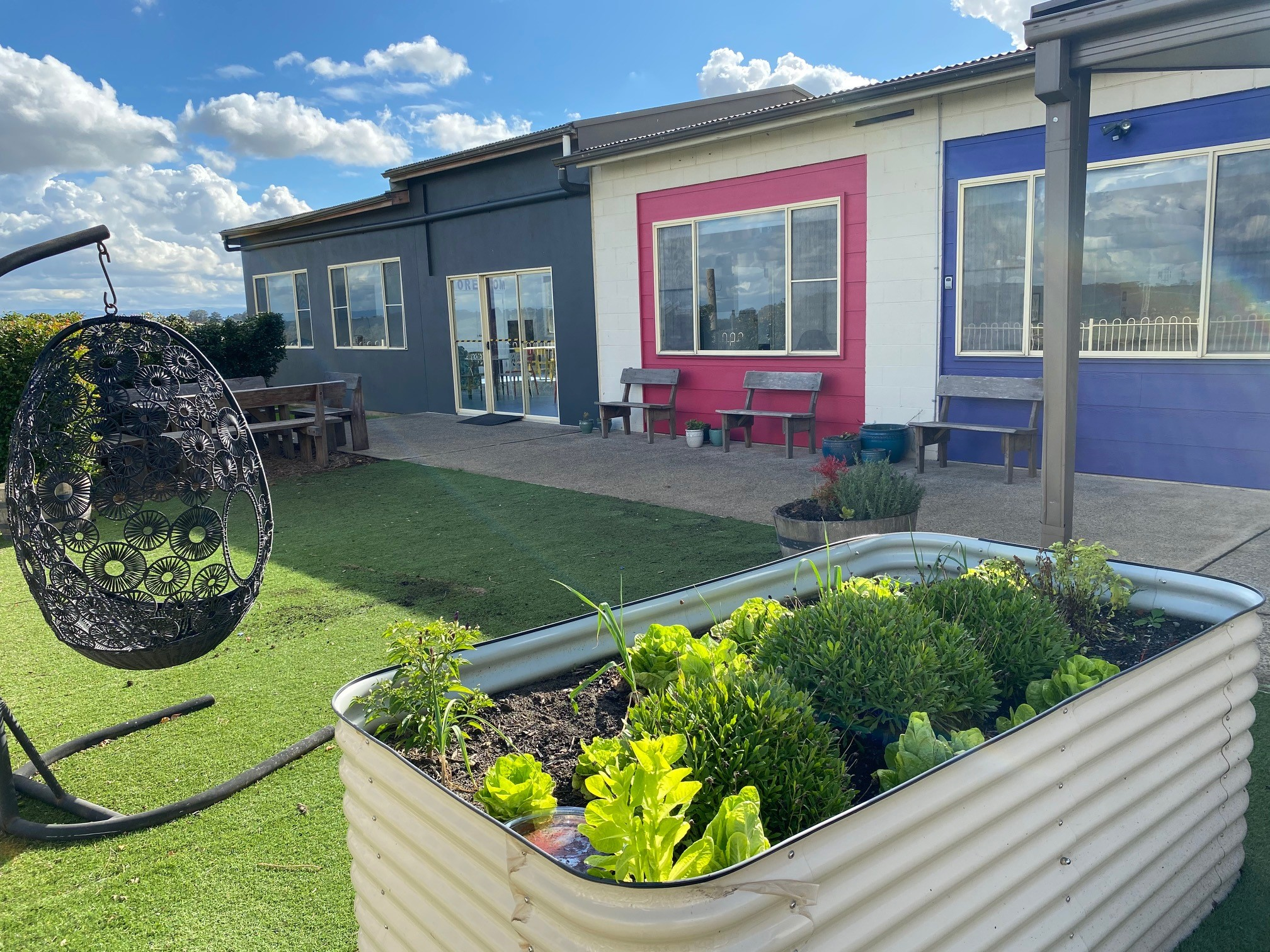 Faux grass area with seating and a vegetable planter box in the alfresco area at the McCall Gardens community participation program centre.